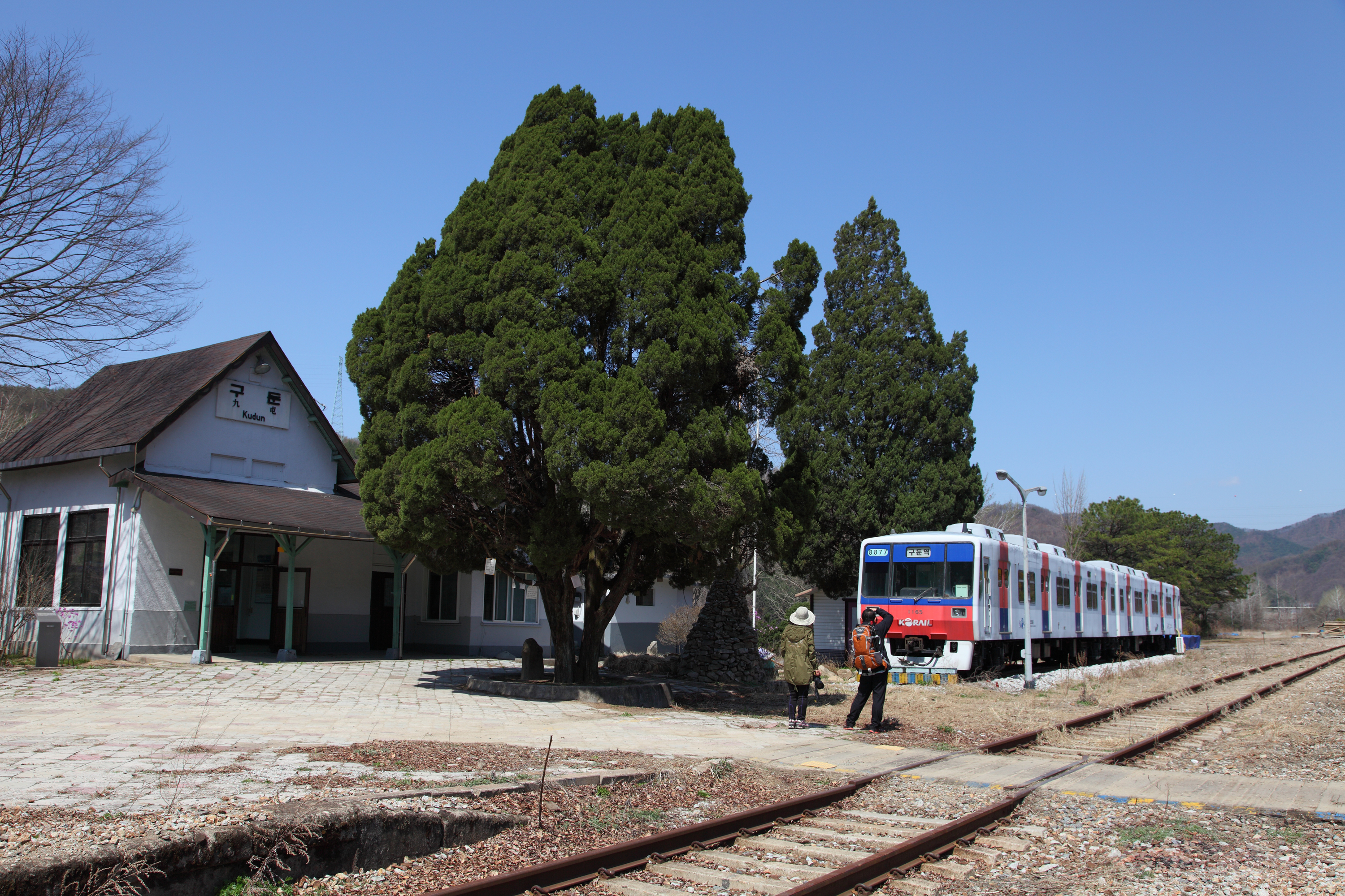 A front view of Kudun Station and ther is actual old subway next to the station. And two people are taking photos of it.