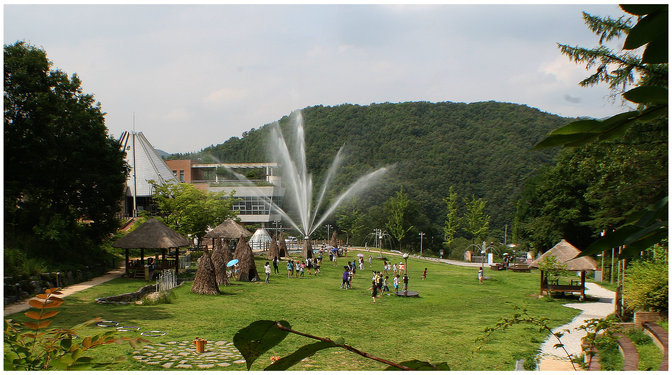 An open view of Sonagi Village with various small shanties. A big fountain is operating now and lots of people are looking around there.