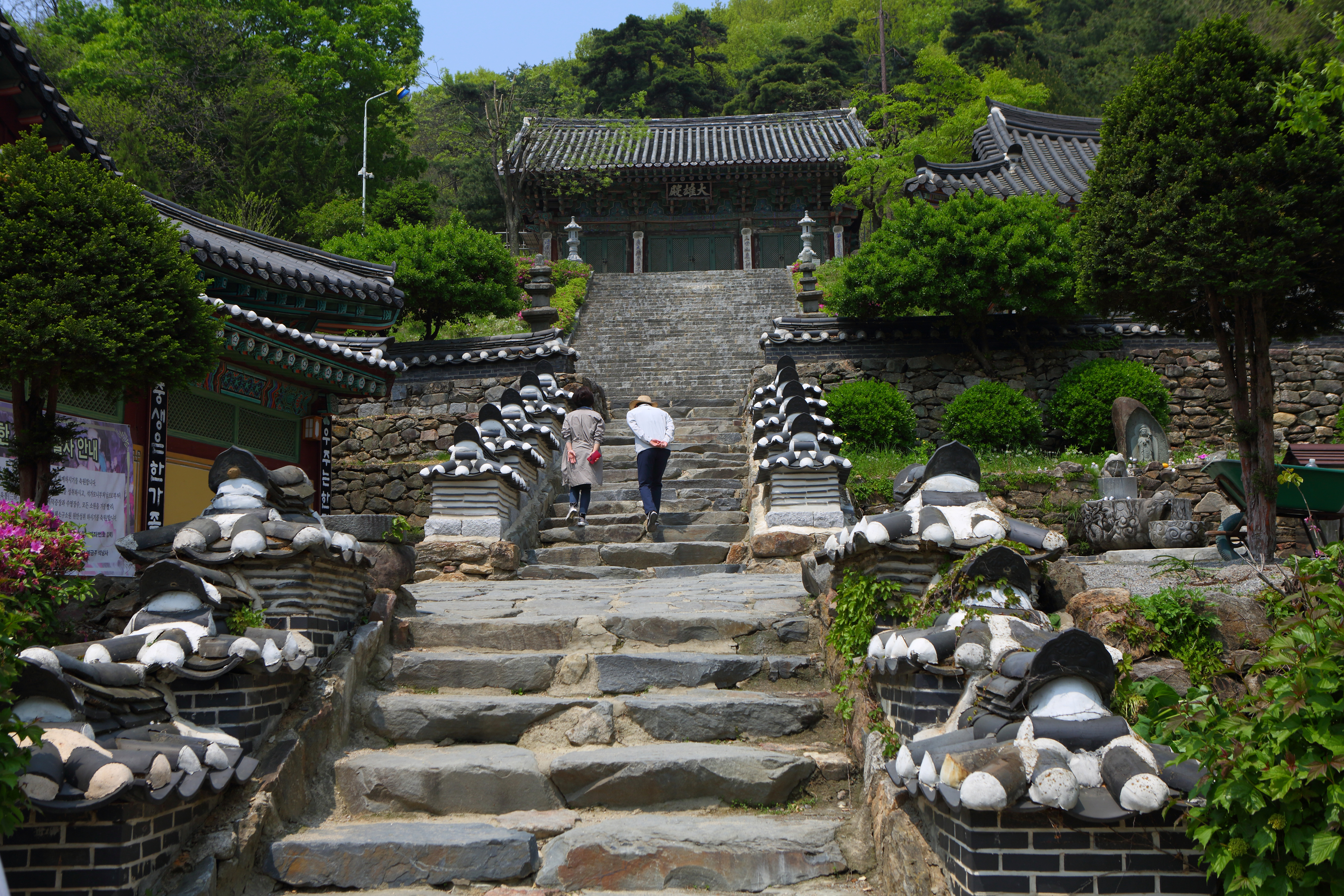 A front view of the stone stairs to the main temple of  Seoknamsa Temple. It's surrounded by greenish nature and hamonized with them very well. Two people are walking on the stairs.